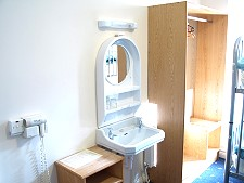 Hairdryer, hand basin and wardrobe